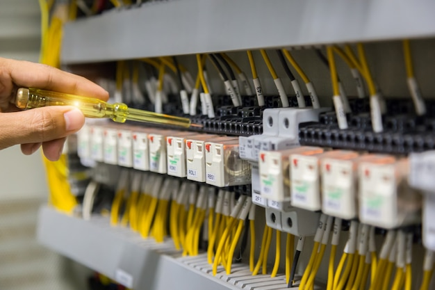 Mãos dos eletricistas que testam atual elétrico no painel de controle. Foto Premium
