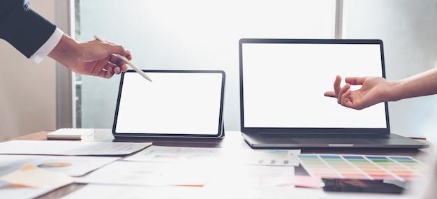 Mãos dos executivos que trabalham no laptop e na tabuleta no escritório criativo. Foto Premium