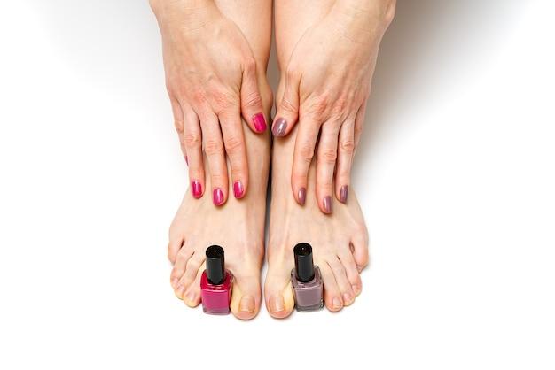 Mãos e pernas de mulher segurando esmalte Foto Premium