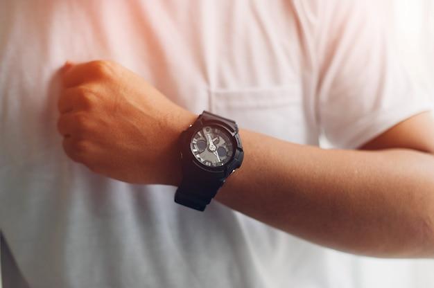 Mãos e relógios pretos de homens jovens que gostam de relógios conceito de tempo Foto Premium