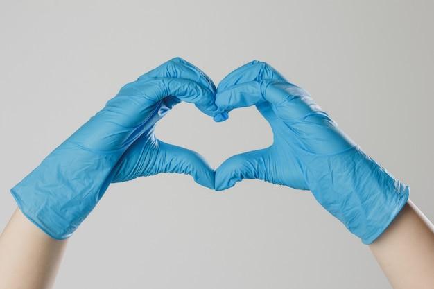 Mãos em luvas de látex médicas. as mãos formam uma forma de coração. o gesto simboliza a declaração de amor. Foto Premium