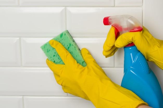 Mãos em luvas de proteção de borracha com detergente e esponja Foto Premium