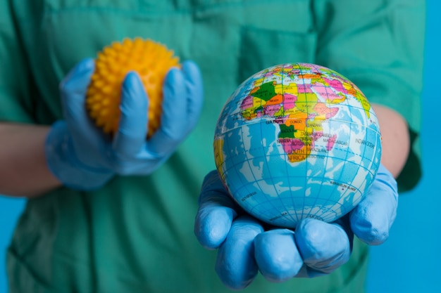 Mãos em luvas médicas seguram uma maquete do planeta terra em primeiro plano e uma maquete do vírus, símbolo da pandemia global, o conceito Foto Premium