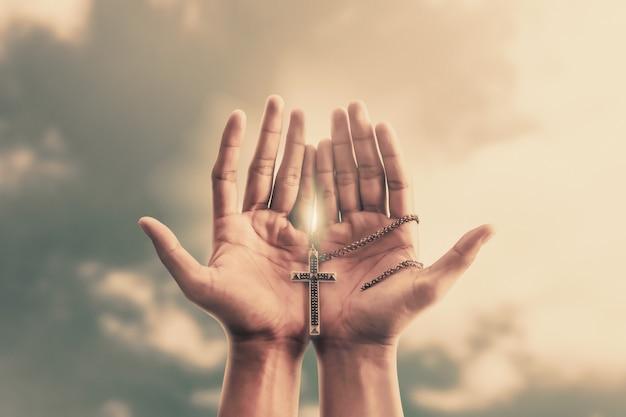 Mãos em oração seguram um crucifixo ou uma cruz de colar de metal com fé na religião e crença em deus Foto Premium