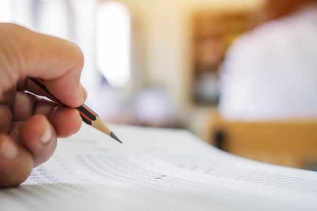 Mãos estudantes, levando, exames, escrita, quarto exame, com, segurando, lápis, ligado, óptico, forma Foto Premium