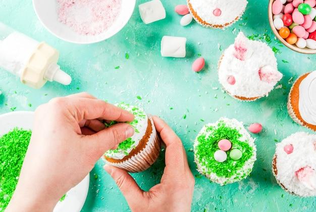 Mãos fazendo cupcakes de páscoa com orelhas de coelho Foto Premium