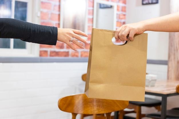 Mãos fazendo uma entrega de fast food Foto Premium
