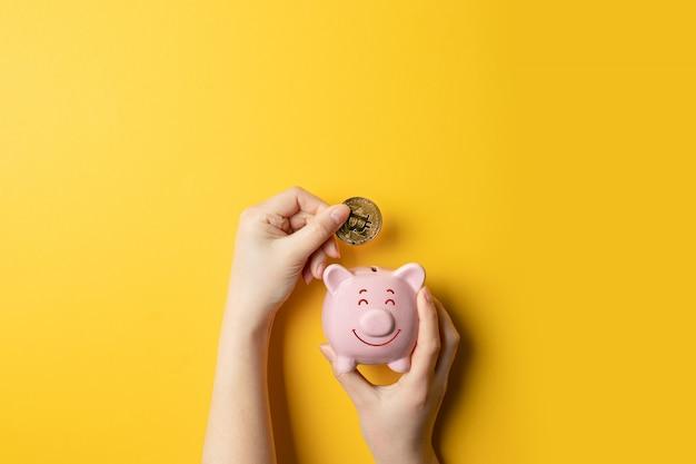Mãos fêmeas que guardam o mealheiro piggy e que põem o dinheiro do bitcoin no banco piggy. Foto Premium