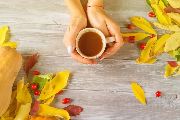 Mãos fêmeas que guardam uma xícara de café em um fundo de madeira cinzento com espaço da cópia. vista do topo Foto Premium