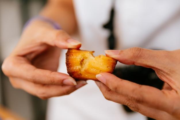 Mãos fêmeas que rasgam canelés cozido fresco. Foto Premium