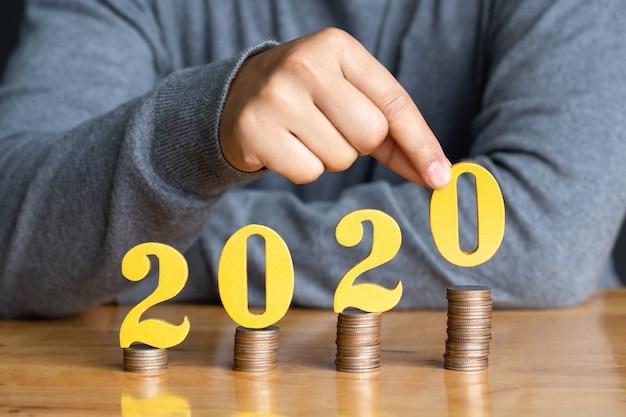 Mãos femininas colocando ouro número de madeira 2020 na pilha de moedas. Foto Premium