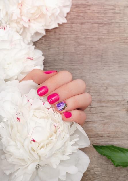 Mãos femininas com design de unhas rosa segurando peônias brancas Foto Premium