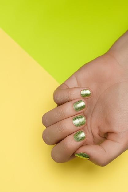 Mãos femininas com design de unhas verdes. mãos bem cuidadas com esmalte verde. mãos femininas em fundo verde Foto gratuita