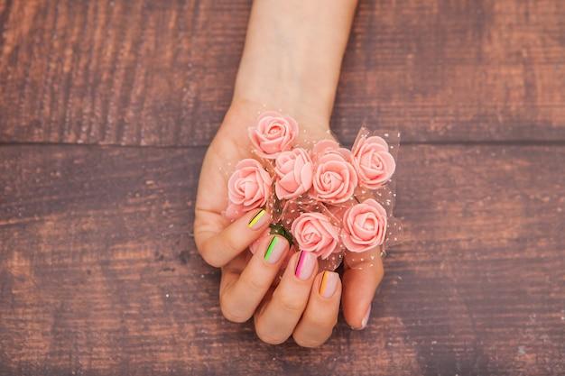 Mãos femininas com manicure moderna e flores cor de rosa em um mogno com tonalidade Foto Premium