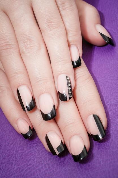 Mãos femininas com manicure preto Foto Premium