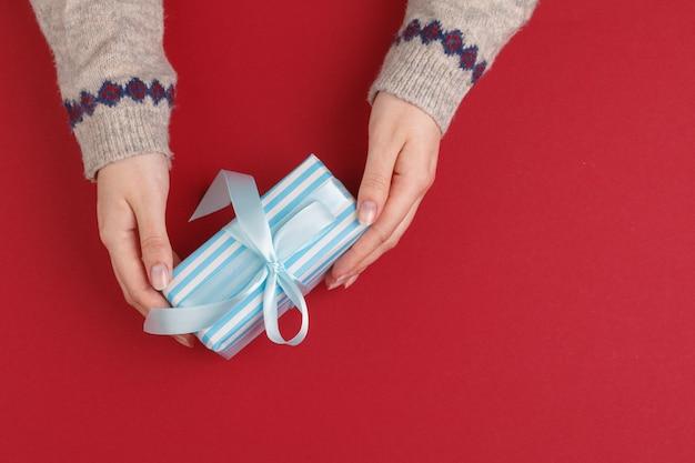 Mãos femininas com presente de natal em vermelho, vista superior, copie o espaço Foto Premium