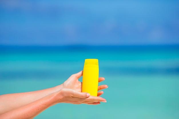 Mãos femininas com suncream garrafa fundo azul mar Foto Premium