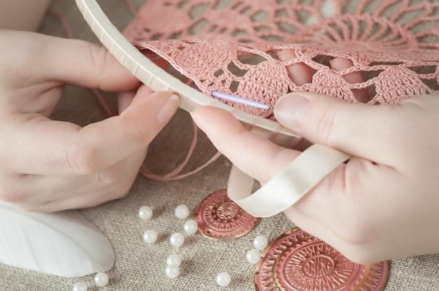 Mãos femininas com tricô rosa Foto Premium