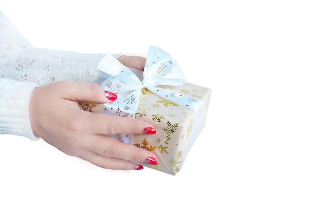 Mãos femininas com um suéter branco seguram uma caixa de presente. Foto Premium