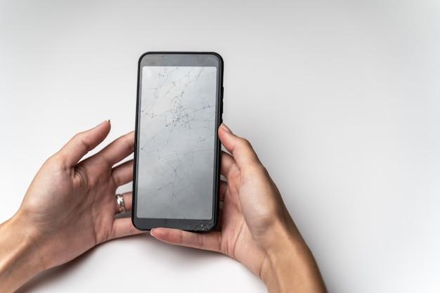 Mãos femininas com um telefone móvel com uma tela quebrada. Foto Premium