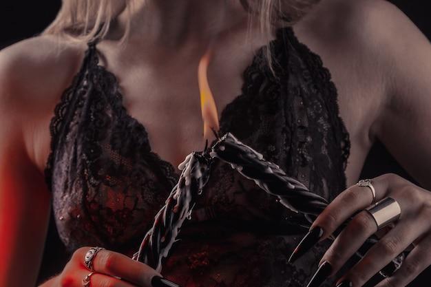 Mãos femininas com unhas compridas segurar velas acesas, bruxaria no dia das bruxas. Foto Premium