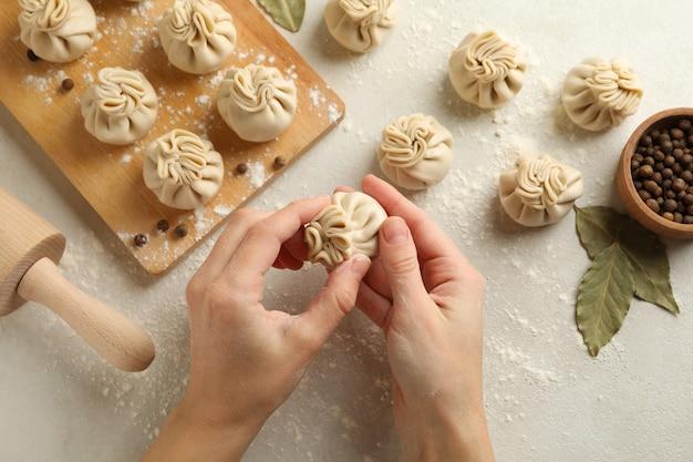 Mãos femininas cozinhando khinkali em fundo branco com ingredientes Foto Premium