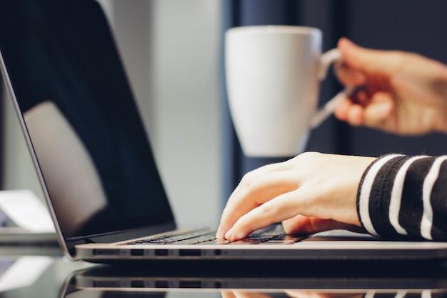 Mãos femininas digitando no teclado do laptop enquanto seguram uma xícara de café, trabalhando em casa conceito Foto gratuita