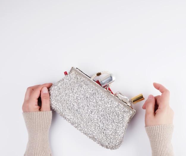 Mãos femininas e uma bolsa de prata com cosméticos Foto Premium