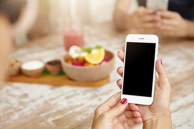 Mãos femininas elegantes com unhas vermelhas limpas, usando telefone celular branco, visualizando feed de notícias através da sua conta nas redes sociais Foto gratuita