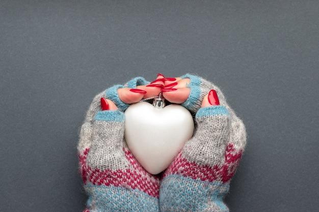 Mãos femininas em luvas de malha, com coração fosco e unhas vermelhas brilhantes Foto Premium