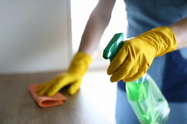 Mãos femininas em luvas desinfetam a mesa em casa Foto Premium