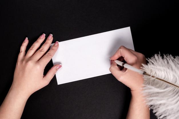 Mãos femininas, escrevendo em papel branco com caneta vitage de penas com copyspace Foto Premium