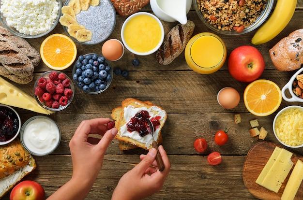 Mãos femininas espalhando manteiga e geléia no pão. ingredientes de pequeno-almoço saudável, quadro de comida. granola, nozes, frutas, frutas, leite, iogurte, suco, queijo. Foto Premium