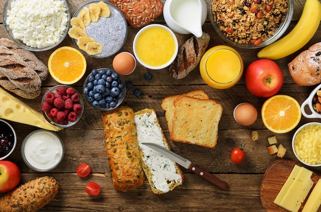 Mãos femininas espalhar manteiga no pão. mulher cozinhando o café da manhã. ingredientes de pequeno-almoço saudável, quadro de comida. Foto Premium