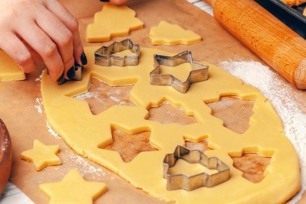 Mãos femininas fazendo biscoitos de massa fresca em casa Foto Premium