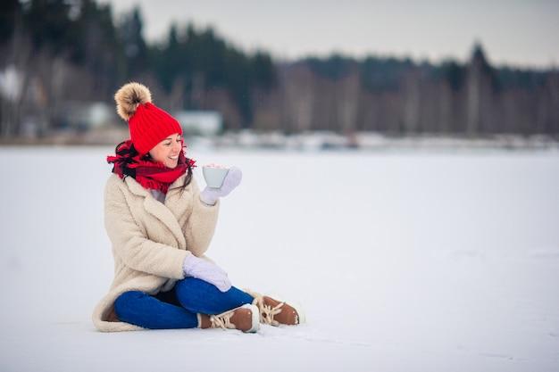 Mãos femininas holdink branco xícara de café com marshmallows brancos e rosa Foto Premium