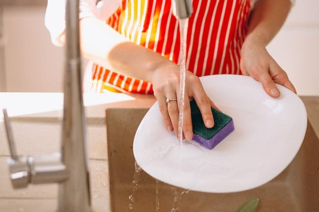 Mãos femininas lavar doshes de perto Foto gratuita