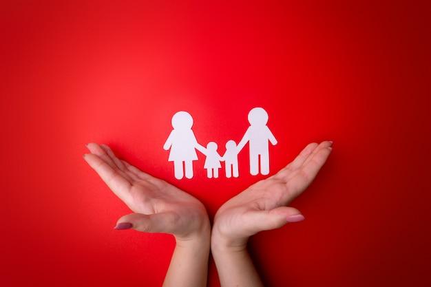 Mãos femininas macias com um símbolo de família recortadas em papel branco. protegendo os direitos das pessoas e das minorias sexuais Foto Premium