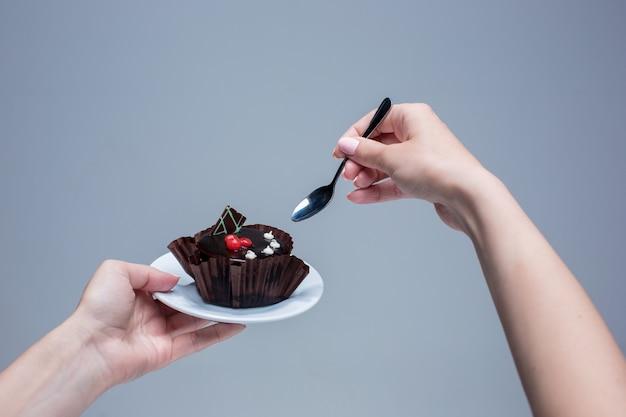 Mãos femininas, mantendo o bolo com a colher em cinza Foto gratuita