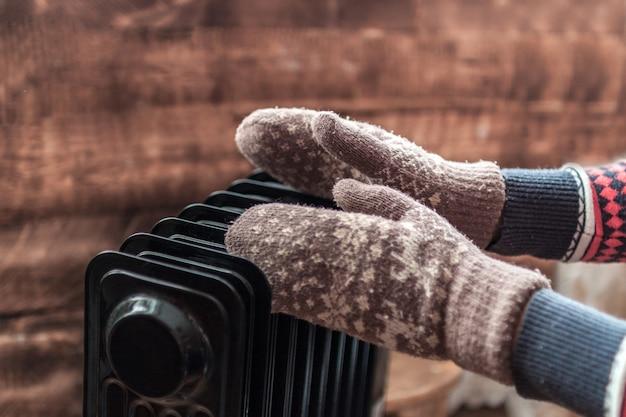 Mãos femininas no natal, luvas quentes de inverno no aquecedor. mantenha quente no inverno, nas noites frias. estação de aquecimento Foto Premium