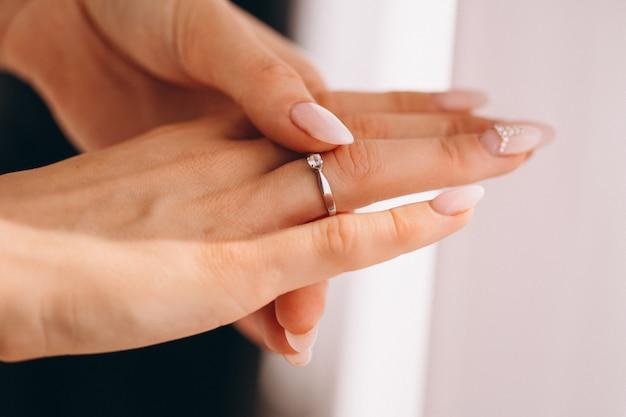 Mãos femininas perto com anel de casamento Foto gratuita