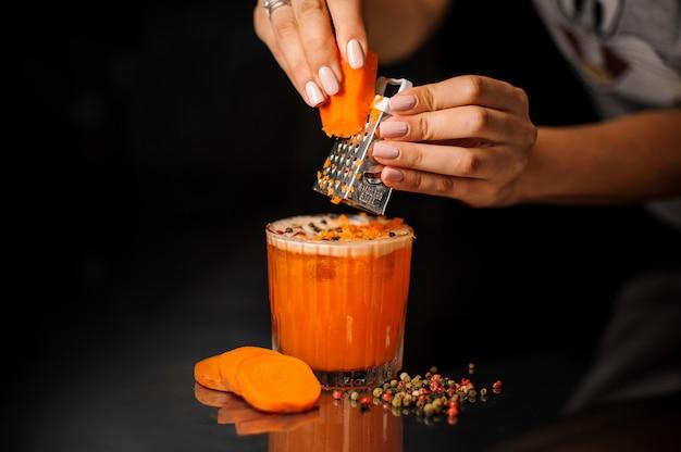 Mãos femininas, ralar as cenouras no cocktail saudável com pimenta Foto Premium
