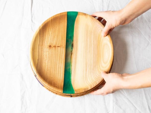 Mãos femininas segurando bandejas redondas de madeira Foto Premium