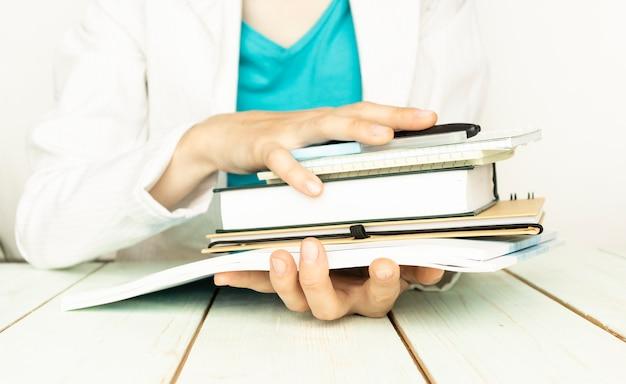 Mãos femininas segurando cadernos, isolados no fundo branco Foto Premium