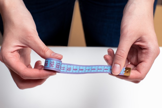 Mãos femininas segurando fita métrica azul Foto Premium