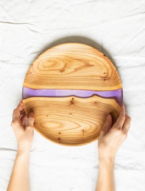 Mãos femininas segurando uma bandeja redonda de madeira com uma inserção de resina lilás Foto Premium