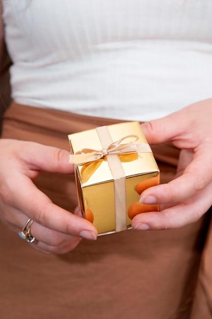 Mãos femininas segurando uma caixa de presente ouro, presente de feriado, aniversário, natal, pai ou mãe, dia dos namorados close-up Foto Premium