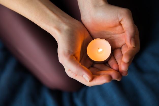 Mãos femininas segurando uma vela acesa Foto gratuita