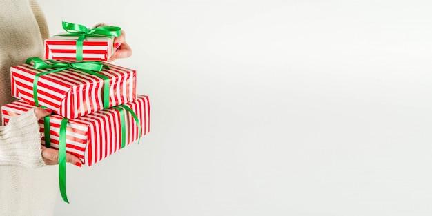Mãos femininas segurar caixas de presente de natal, champanhe e taças Foto Premium