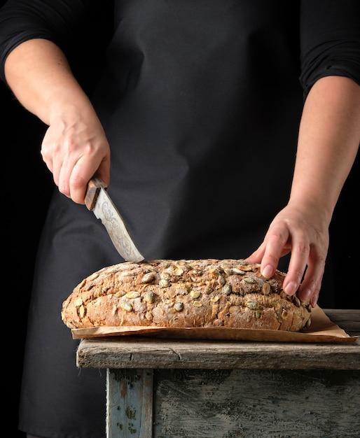 Mãos femininas segurar oval cozido pão de centeio com sementes de abóbora Foto Premium